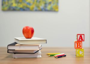 Books, apple, coloured pencils and ABC wooden blocks