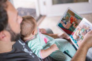 parent reading story book with young child.
