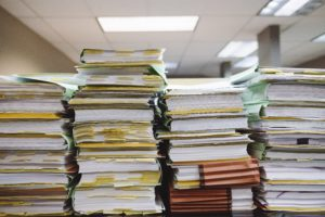Large stacks of books and files on a table.